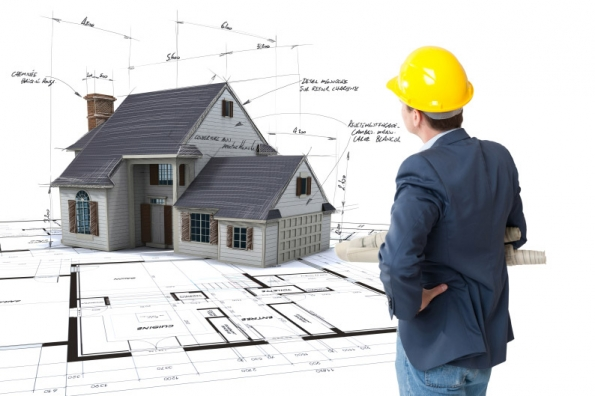 surveyor looking at house plan & model